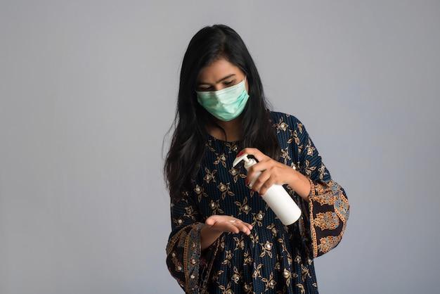 Portrait de jeune fille à l'aide ou montrant un gel désinfectant d'une bouteille pour le nettoyage des mains.