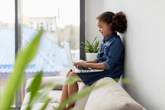 Portrait de jeune fille à l'aide de l'ordinateur portable