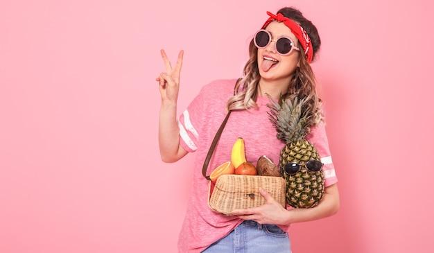 Portrait d'une jeune fille avec des aliments sains, des fruits, sur un mur rose