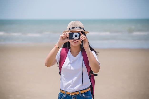 Portrait d'une jeune fille avec un appareil photo sur la plage