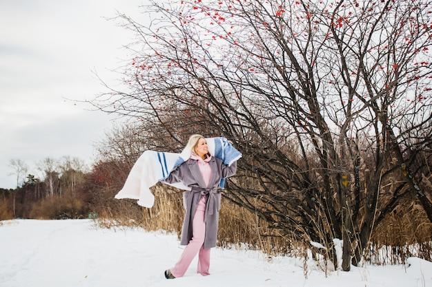 Portrait d'une jeune fille d'apparence européenne sur une promenade d'hiver, herbe, forêt, champ, chapeau, santé. fille avec un plaid, enveloppé dans un plaid, écharpe