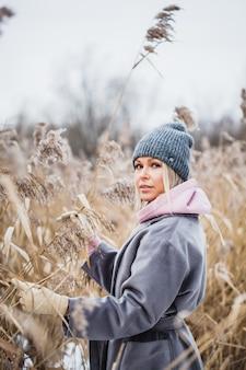 Portrait d'une jeune fille d'apparence européenne sur une promenade d'hiver, herbe, forêt, champ, chapeau, santé