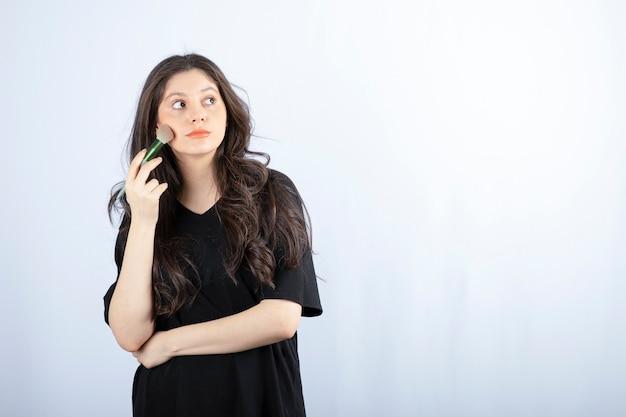 Portrait de jeune fille appliquant le fard à joues sur ses joues sur fond blanc.