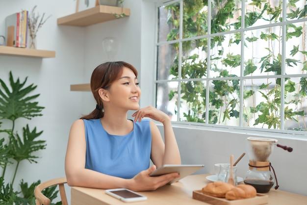 Portrait d'une jeune fille asiatique heureuse à l'aide d'une tablette assise derrière la fenêtre le matin
