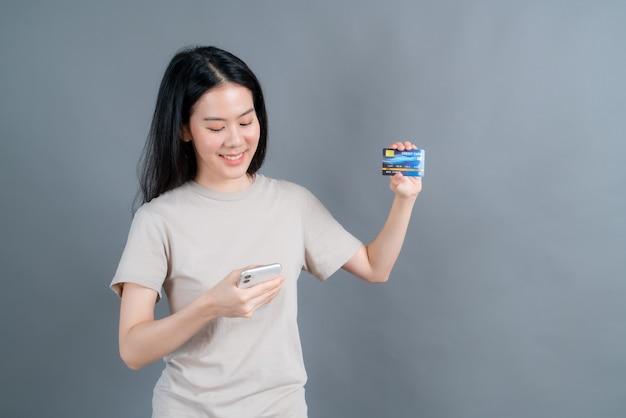 Portrait d'une jeune fille asiatique heureuse montrant une carte de crédit en plastique tout en tenant un téléphone mobile sur un mur gris