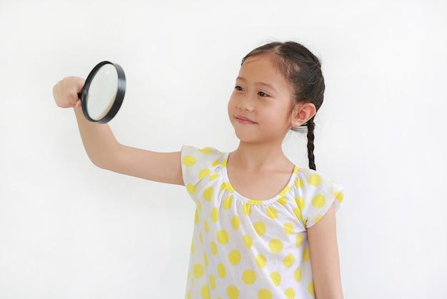 Portrait d'une jeune fille asiatique regardant à travers une loupe à côté sur fond blanc.