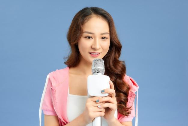 Portrait de jeune fille asiatique tenant un microphone sur fond bleu.
