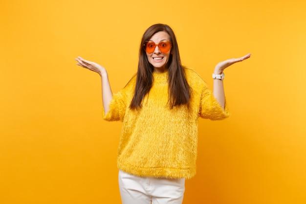Portrait d'une jeune fille assez coupable en pull de fourrure pantalon blanc coeur lunettes orange écartant les mains isolées sur fond jaune vif. les gens émotions sincères, concept de style de vie. espace publicitaire.