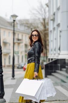 Portrait de jeune fille assez élégante tenant les sacs à provisions et impatient de bonne humeur. shopping idéal.