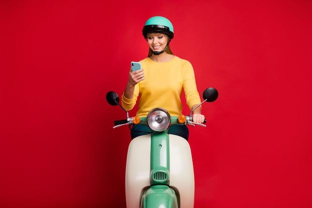Portrait de jeune fille assise sur un cyclomoteur à l'aide de cellule lire sms sur fond rouge