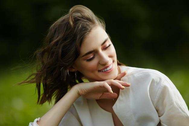 Portrait d'une jeune fille assise dans un champ sur l'herbe de printemps parmi les fleurs de pissenlit. cheerful girl bénéficie d'un temps printanier ensoleillé