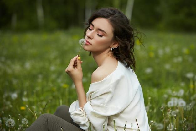 Portrait d'une jeune fille assise dans un champ sur l'herbe de printemps parmi les fleurs de pissenlit. la fille gaie apprécie le temps ensoleillé de ressort. beauté naturelle d'une femme, cosmétiques naturels