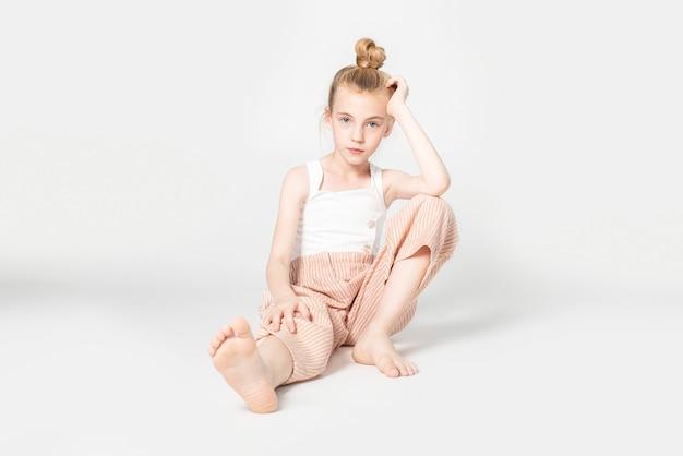 Portrait de jeune fille assise sur le sol du studio avec du blanc