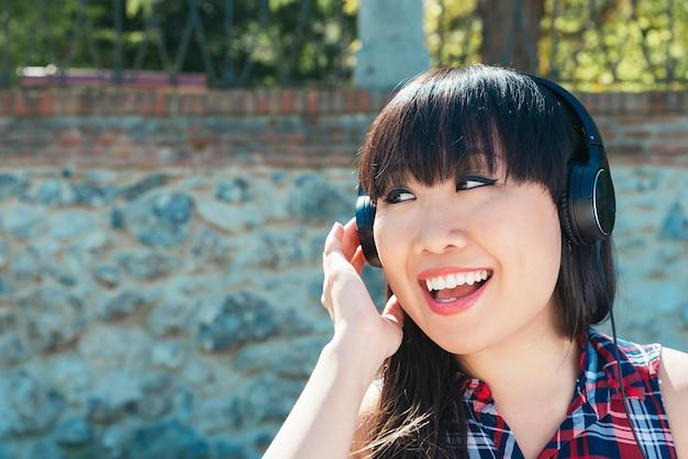 Portrait de jeune fille attirante chinoise en milieu urbain écoutant de la musique avec des écouteurs