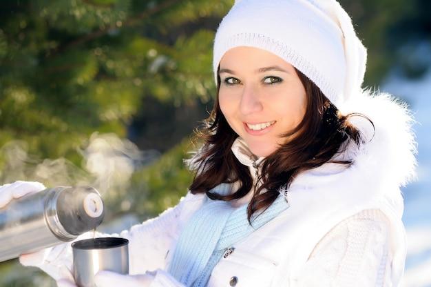 Portrait de jeune fille au chapeau blanc et gants tient une tasse en métal près du visage