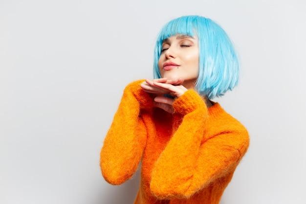 Portrait de jeune fille aux cheveux bleus en pull orange, main dans la main sous le menton sur fond blanc.