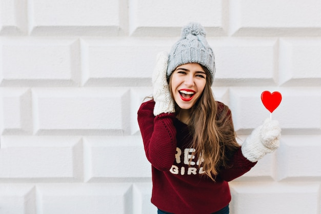 Portrait jeune fille aux cheveux longs en bonnet tricoté et pull marsala avec sucette coeur rouge sur mur gris. elle porte des gants blancs et chauds, en riant.
