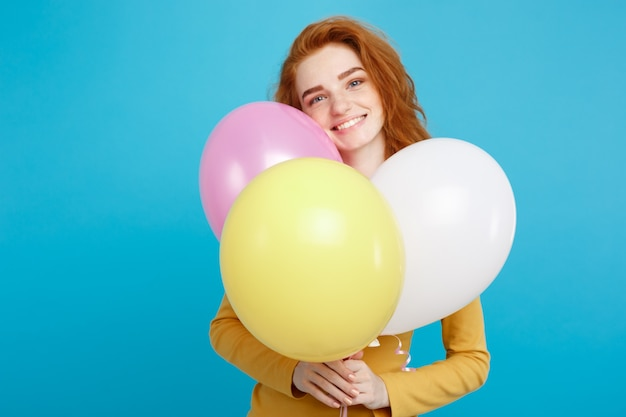 Portrait jeune fille aux cheveux roux avec des ballons colorés.