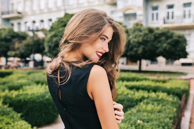 Portrait de jeune fille aux longs cheveux bouclés posant sur le bouvillon sur la cour