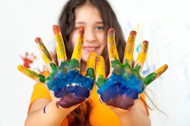 Portrait d'une jeune fille aux paumes multicolores. retour à l'école.