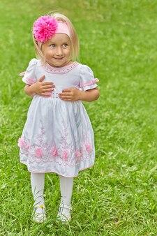 Portrait d'une jeune fille aux yeux sournois dans une robe et un arc sur la tête. l'émotion d'un enfant dans la rue