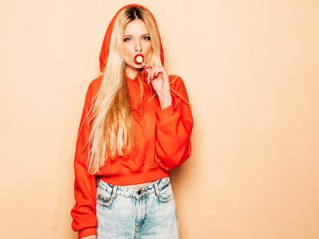 Portrait de jeune fille belle hipster belle mauvaise à capuche rouge à la mode et boucle d'oreille dans son nez. modèle positif léchant des bonbons de sucre ronds
