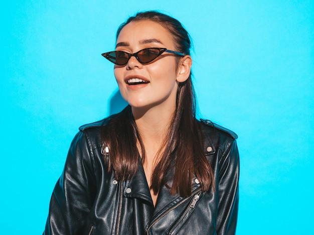 Portrait de jeune fille belle hipster belle mauvaise en veste de cuir noir tendance été et lunettes de soleil. sexy femme insouciante isolée sur bleu. brunette modèle posant