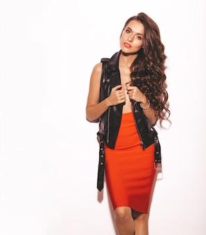Portrait de jeune fille belle hipster en jupe rouge tendance d'été et veste en cuir noir. sexy femme insouciante isolée sur blanc. modèle brune avec maquillage et coiffure