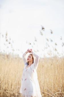 Portrait de jeune fille belle à la robe blanche dans le champ de blé, à pied, sans soucis.