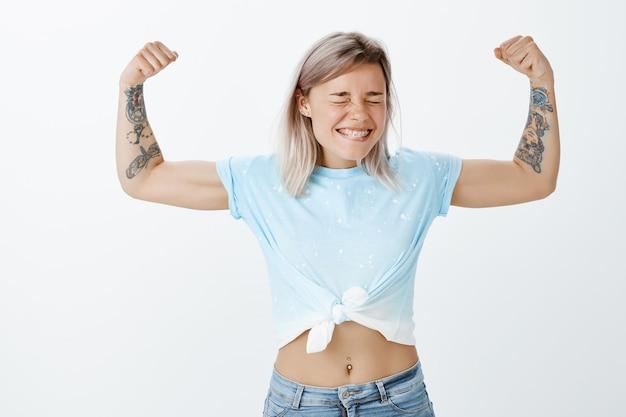 Portrait de jeune fille blonde active joyeuse posant dans le studio