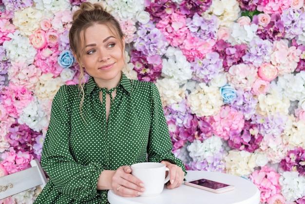 Portrait de jeune fille blonde assise à la table dans le café sur un fond floral avec une tasse de thé