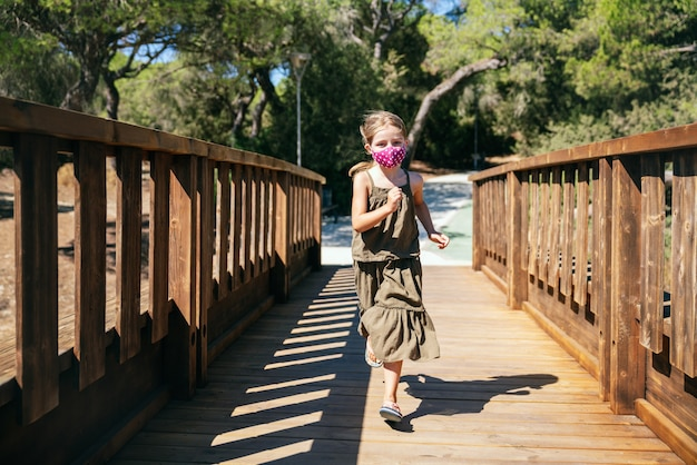 Portrait de jeune fille blonde aux yeux bleus avec masque facial en vacances qui traverse un pont en bois avec des pins avec une robe verte au milieu de la pandémie de coronavirus
