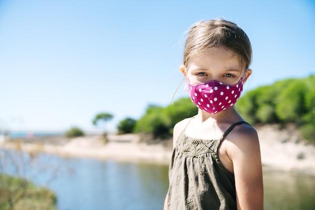 Portrait d'une jeune fille blonde aux yeux bleus portant un masque facial en vacances sur une plage de pins avec un visage sérieux dans une robe verte au milieu d'une pandémie de coronavirus