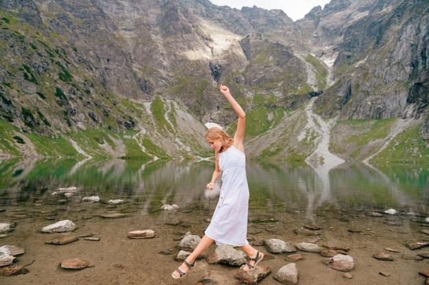 Portrait de jeune fille blonde en équilibre sur la pierre dans le lac entre les montagnes.