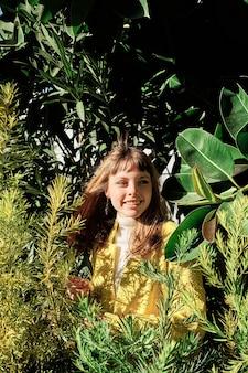 Un portrait d'une jeune fille blonde de race blanche aux yeux bleus parmi les plantes vertes du parc