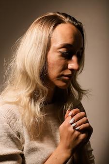 Portrait d'une jeune fille blonde triste sans maquillage avec ses cheveux vers le bas les mains jointes près de son visage