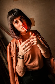 Portrait d'une jeune fille brune allumant une cigarette 12
