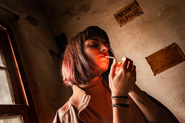 Portrait d'une jeune fille brune allumant une cigarette 17