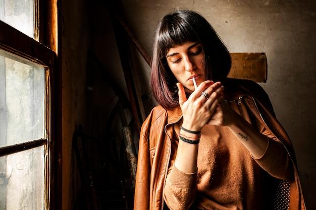 Portrait d'une jeune fille brune allumant une cigarette
