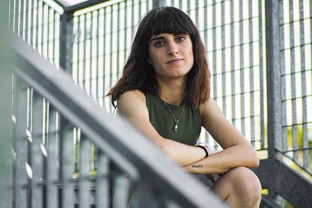 Portrait de jeune fille brune assise sur les escaliers urbains