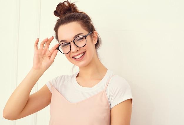 Portrait de jeune fille brune belle modèle de fille avec du maquillage nude dans des vêtements de hipster rose d'été coloré posant près du mur. regardant joyeusement