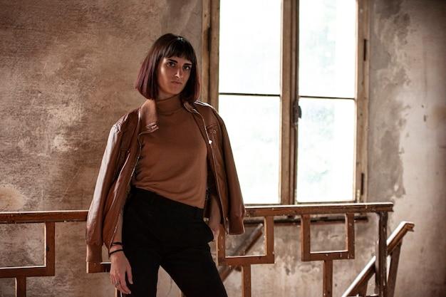 Portrait d'une jeune fille brune dans une maison abandonnée, image en basse lumière