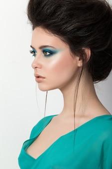 Portrait de jeune fille brune dans une robe turquoise à la recherche de la distance