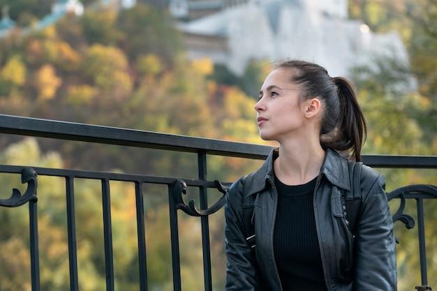 Portrait de jeune fille brune sur fond de parc. belle jeune femme au repos en plein air.