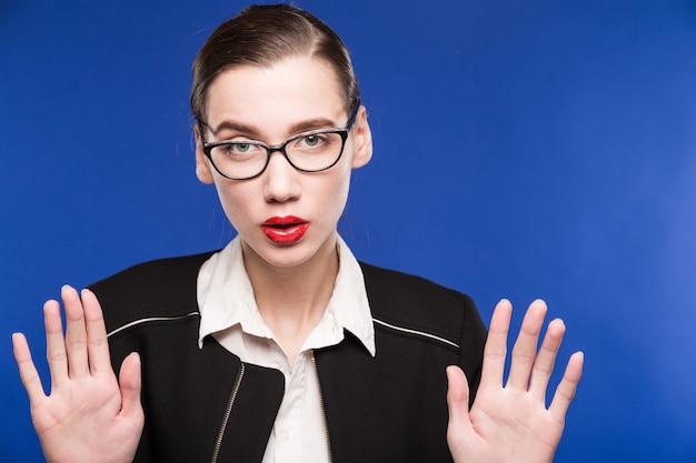 Portrait de jeune fille brune à lunettes avec les mains près du visage