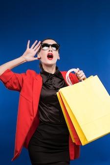 Portrait de jeune fille brune à lunettes de soleil avec des sacs dans les mains