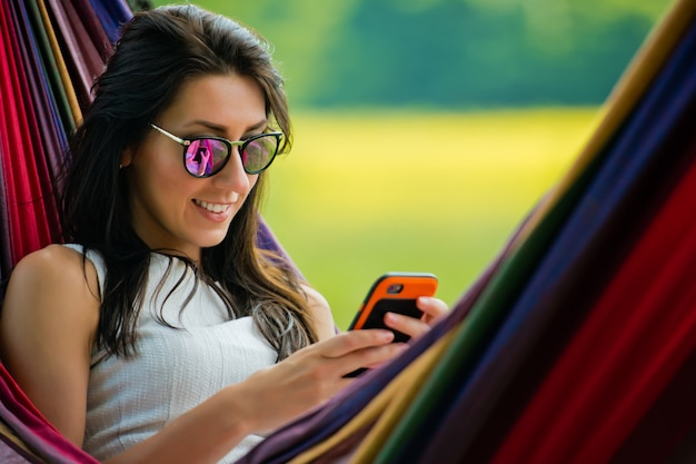 Portrait de jeune fille brune à lunettes de soleil se trouve dans un hamac et joue avec le téléphone mobile. fermer.