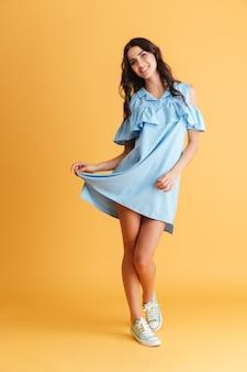 Portrait d'une jeune fille brune souriante en robe bleue isolée