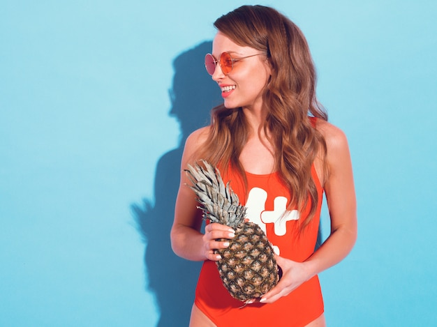Portrait de jeune fille brune souriante en vêtements de bain d'été rouge et lunettes de soleil rondes. femme sexy avec ananas frais. modèle positif posant