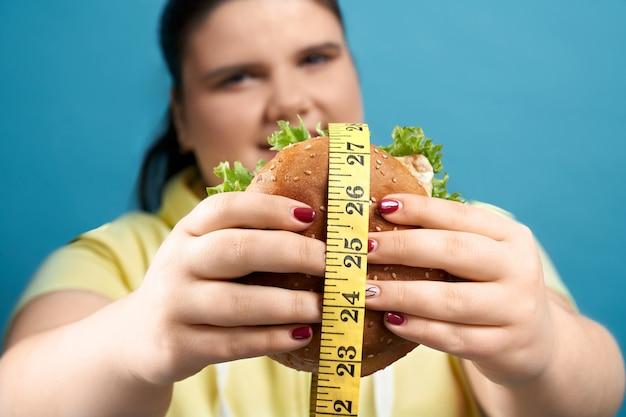 Portrait de jeune fille brune surdimensionnée gardant un hamburger fraîchement cuit recouvert de ruban à mesurer jaune et regardant la caméra. isolé sur fond bleu. concept de malbouffe et de mauvaise alimentation
